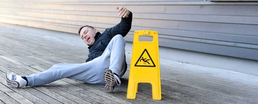 A man lying on the ground after a slip and fall accident.